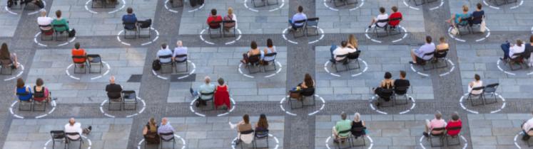 Des personnes assistent, assis, à un concert en plein air