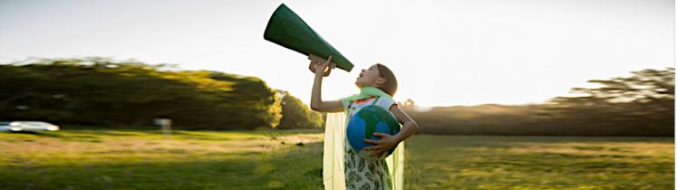 Une jeune fille parle dans un porte-voix dans un pré avec un globe terrestre sous le bras