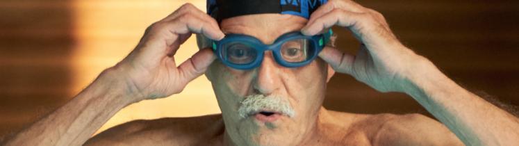 Image d'un homme âgé chaussant ses lunettes de natation