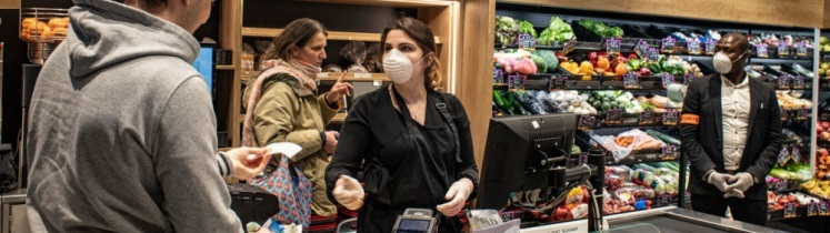 Une caissière dans un supermarché face à une cliente