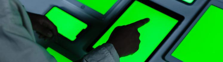 Une main d'homme désigne plusieurs écrans de tablettes numériques à fond vert