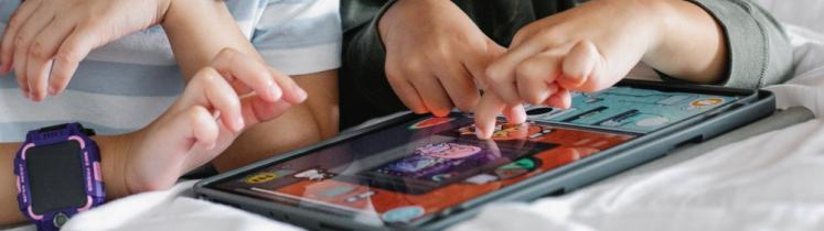 Deux enfants jouent sur une tablette