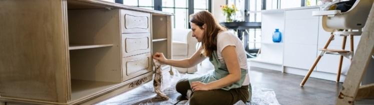Une femme repeint un meuble